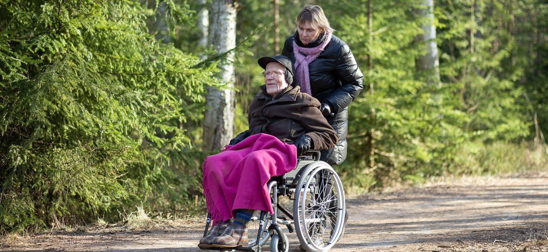 Valokuva yrityksestä Dementiakoti Villa Tapiola: hoitaja ulkoilemassa lähimetsässä pyörätuolissa olevan asukkaan kanssa
