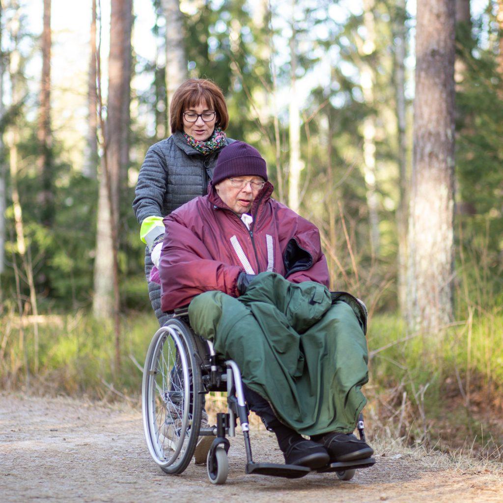 Valokuva yrityksestä Dementiakoti Villa Tapiola: hoitaja ja asukas lähimetsän lenkkipolulla