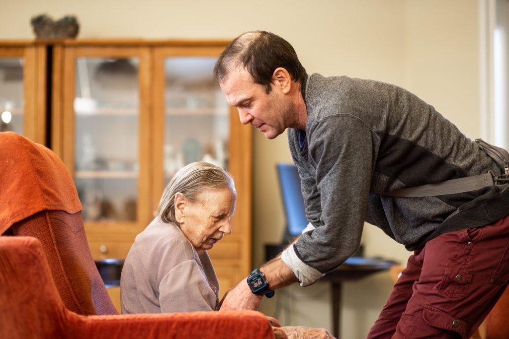 Valokuva yrityksestä Dementiakoti Villa Tapiola: hoitaja auttaa asukasta nousemaan nojatuolista
