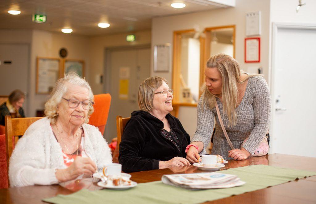 Valokuva yrityksestä Dementiakoti Villa Tapiola: hoitaja ja asukas keskustelevat iltapäiväkahveilla