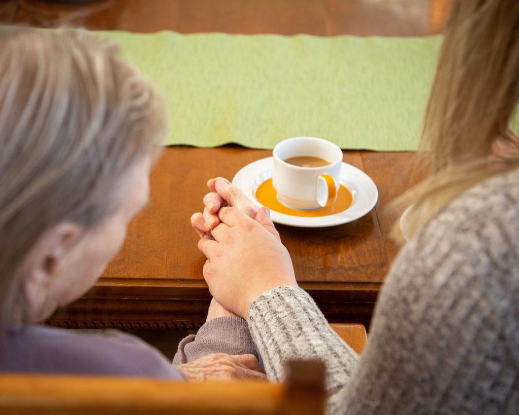 Valokuva yrityksestä Dementiakoti Villa Tapiola: käsi kädessä kahvitauon aikana