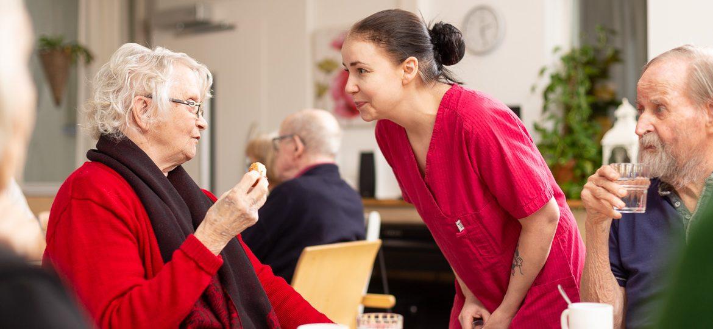 Valokuva yrityksestä Varpulan ja Vuokselan hoivakodit: hoitaja ja asukas keskustelevat iltapäiväkahveille