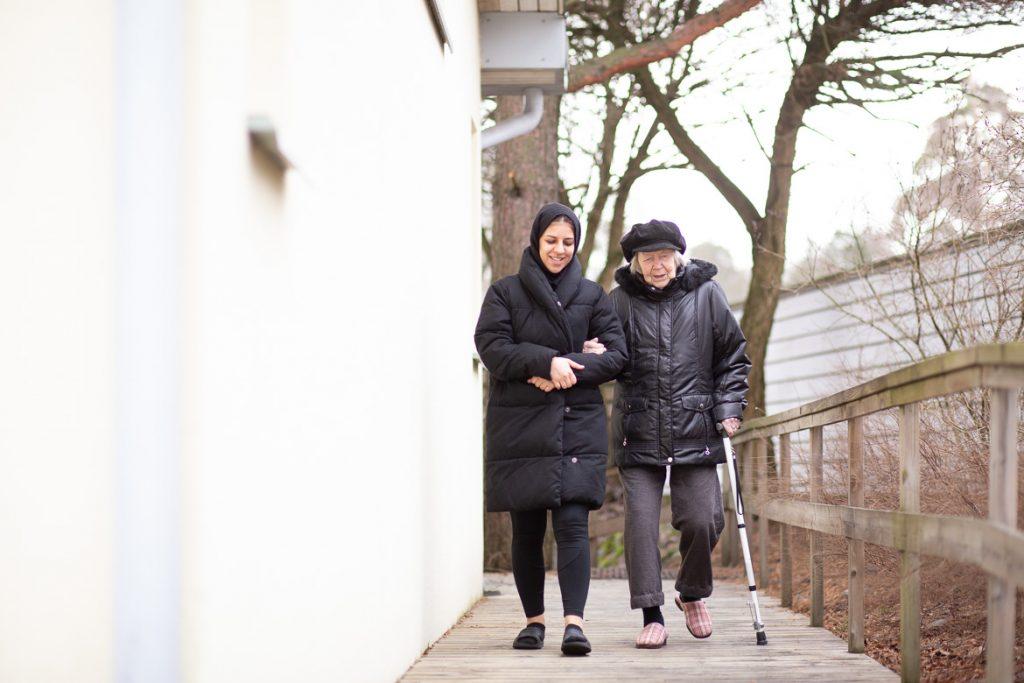 Valokuva yrityksestä Varpulan ja Vuokselan hoivakodit: hoitaja ja asukas kävelyllä ulkona